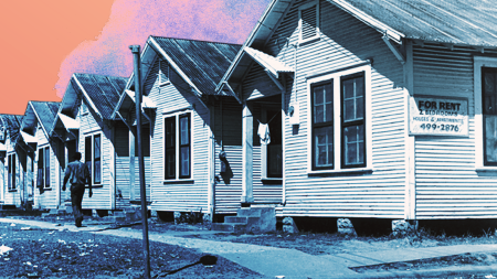 photograph of a row of houses with a man walking on the sidewalk