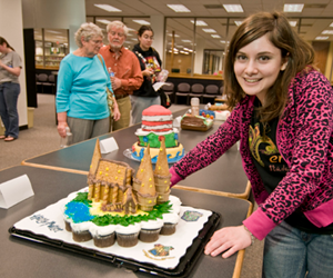 Image of girl standing next to Hogwarts Castle made from cupcakes, graham crackers, and ice cream cones.
