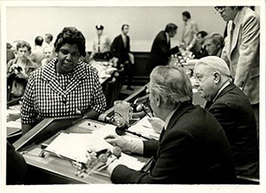 a woman speaking with two men at a courtroom bench