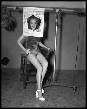 photograph of young woman in a bathing suit looking through a cutout newspaper