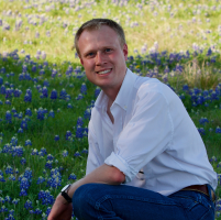 headshot of smiling man in a white shirt kneeling in a field of bluebonnets