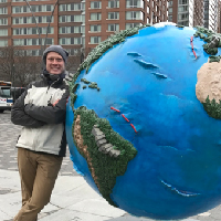 photograph of a smiling man leanig against a world sculpture