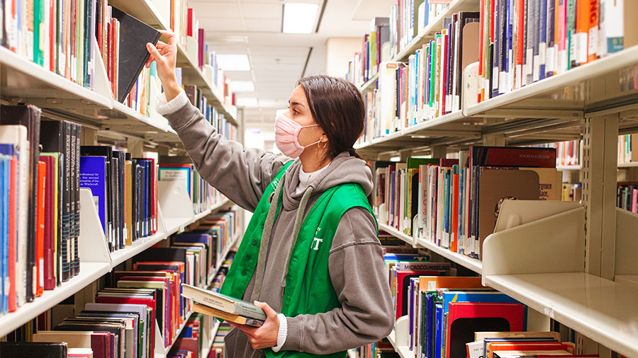 person reaching to books on a shelf