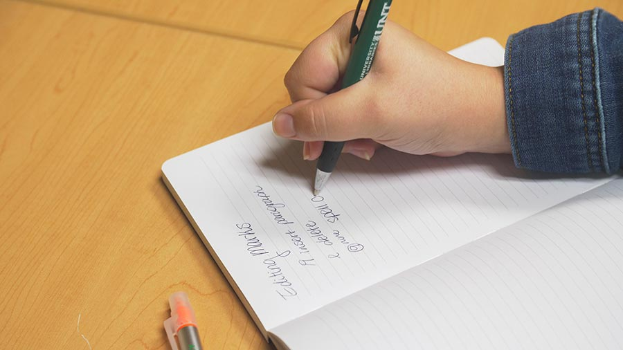 photograph of a hand writing in a notebook