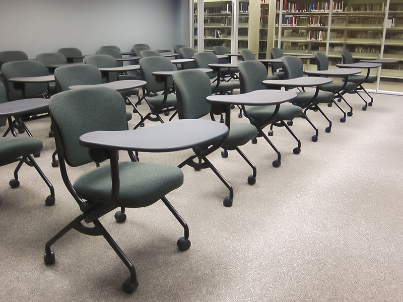 rows of empty black mobile chairs with swivel arm