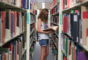 woman standing in the book stacks looking at an open book