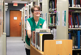 smiling woman pushing book cart