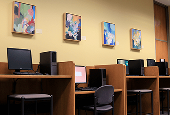 computer workstations with four pieces of art above the stations