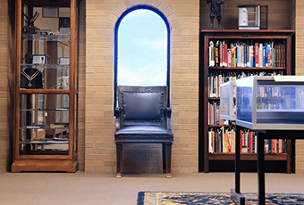 room with a chair and two bookcases
