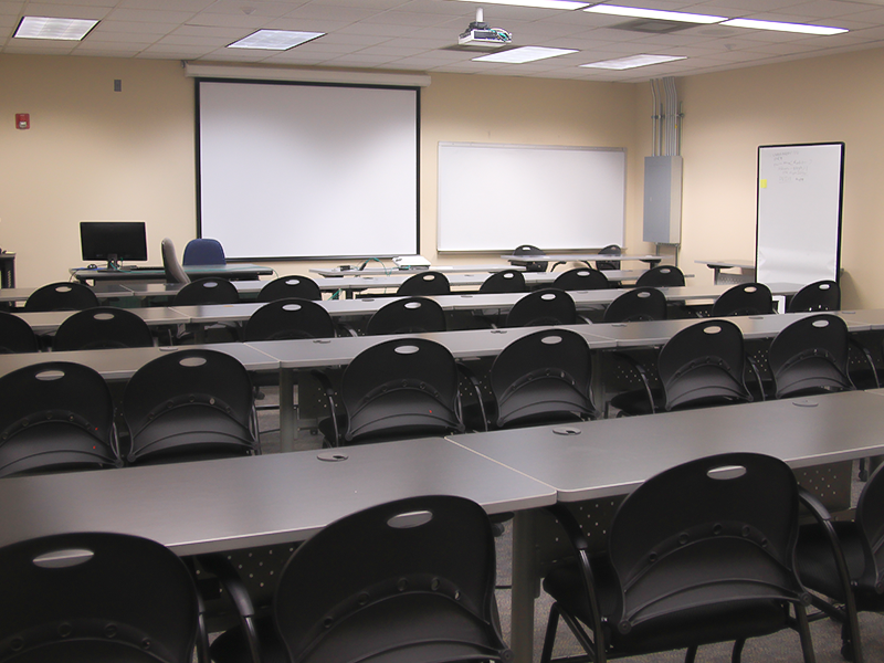 classroom with computers, chairs, and presentation screen