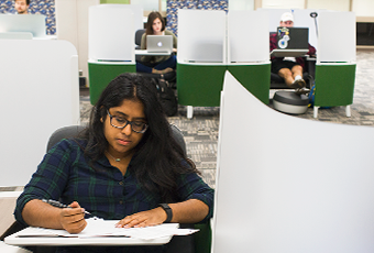 three students in green and white individual study pods