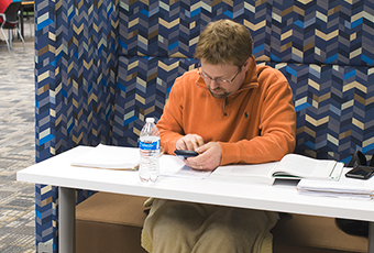 person with open books and phone in an individual study station