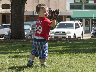 boy catching a baseball with parked cars in the background
