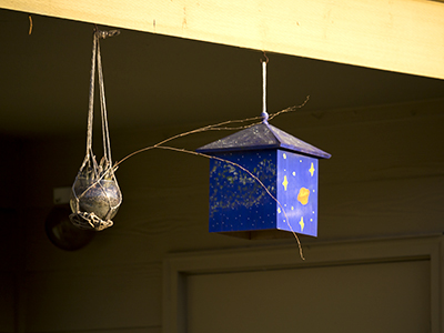 blue birdhouse next to hanging flower pot