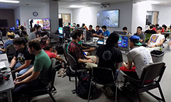 Photo of the Media Library Commons with students playing video games.